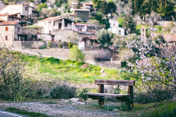 Beautiful spring landscape, a village in the mountains of Cyprus, blue sky, green hills, wooden bench and blossoming almond