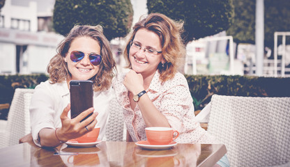 Two young attractive women girlfriends girls are sitting in a cafe, talking, doing online shopping, drinking coffee and looking at the mobile phone