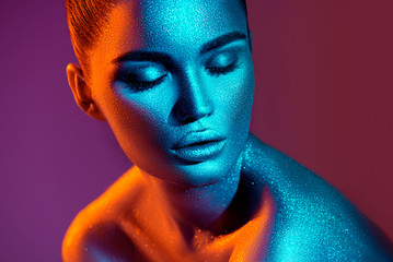 Fashion model woman in colorful bright sparkles and neon lights posing in studio, portrait of beautiful sexy girl. Art design colorful vivid makeup