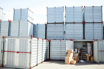 Several large storage containers with heap of boxes near by and work supplies in one of them