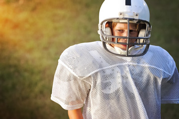 Young boy in a football uniform looking sad
