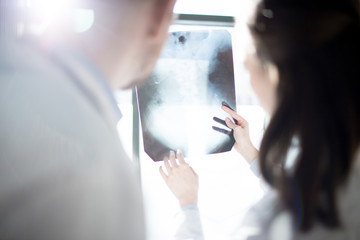 X-ray image held by one of radiologists showing and explaining it to colleague