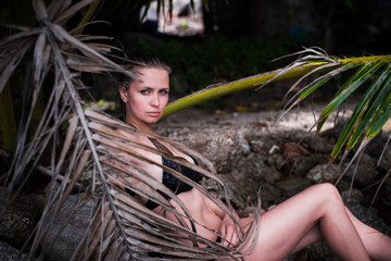 Young sexy woman with ideal body in black swimsuit is posing in palm leaves in jungle