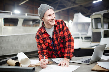 Happy young shipbuilding engineer making new sketch on blueprint by workplace