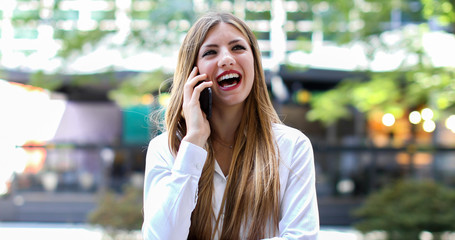 Cheerful young woman on the phone outdoor in a modern urban setting, laughing and looking happy