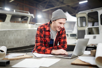 Young contemporary engineer leaning on workplace while looking for online information