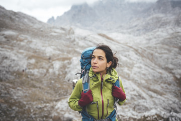 Portrait of attractive young woman mountaineer wearing a green jacket looking to horizon in a rocky scenery