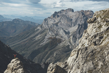 Far view of a hiker in the top of a rock with open arms in Picos de Europa National Park, Spain