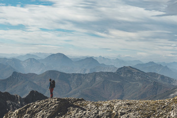 Far view of a hiker standing and looking at the mountains in a scenic landscape in Picos de Europa National Park, Spain