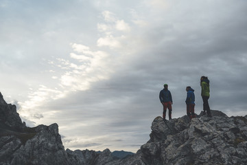 Group of three mountaineers standing and looking at the mountains in a scenic landscape in Picos de Europa National Park, Spain