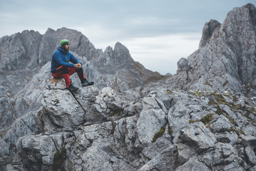 Bearded mountaineer seated and looking at the mountains in a scenic landscape in Picos de Europa National Park, Spain