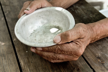 The poor old man's hands hold an empty bowl. The concept of hunger or poverty. Selective focus. Poverty in retirement.Homeless.  Alms