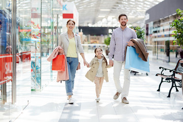 Happy family of shoppers enjoying leisure in large modern trade center on weekend