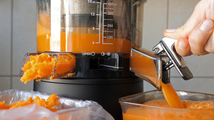 Slow juicer is making fresh carrot and orange juice.