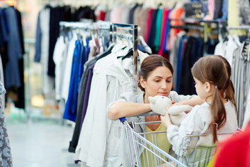 Young female leaning against shopping cart with her daughter while walking around clothing department