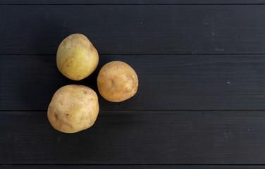 potato on black wood. top view