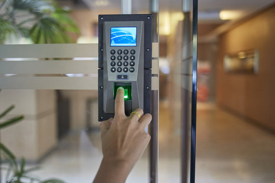 Yong man or woman thumb down finger down on the electronic control machine to access the door