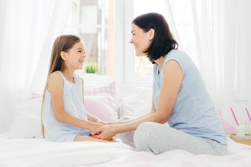 Lovely mother and daughter enjoy togetherness, keep hand together, have pleasant talk, sit on comfortable bed in morning, sit in light bedroom, have good relationships. Family and love concept
