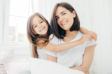 Portrait of happy Caucasian mother with charming smile and her small daughter embraces with love mum, being in good mood, pose on comfortable bed against cozy interior. People and family concept