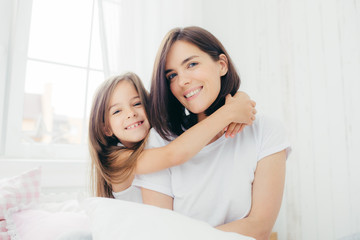 Indoor shot of good looking brunette mother with gentle smile and her small daughter gives hug, enjoy domestic atmosphere, pose against spacious white bedroom interior. Motherhood and family concept