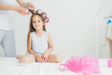 Horizontal shot of cute small daughter sits near her mother who winds curlers, pose against white background, prepares for festive event in kindergarten. Beautiful delighted kid has long hair