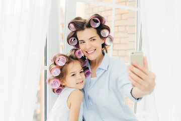 Happy female mother and her small child with curlers on head, pose for making selfie, use modern smart phone, stand near window, prepare for holiday. Happy family, technology, lifestyle concept