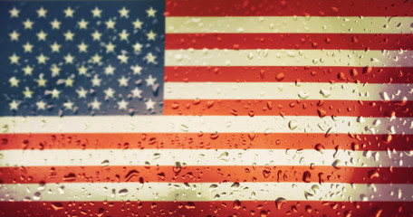 Texture of the USA flag on the glass with drops of rain at dawn.