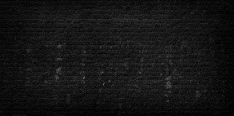 Old cracked black brick wall background.