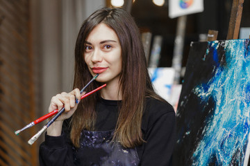 Portrait of a young female artist with brushes for painting.