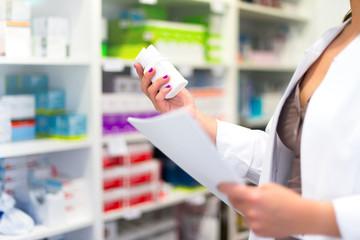 Woman customer in the pharmacy taking a medicine box