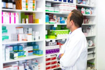 Papiers peints Pharmacie Adult man pharmacist in pharmacy looking for medications