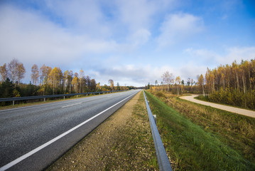 A view of the asphalt country road in Latvia on a clear autumn day