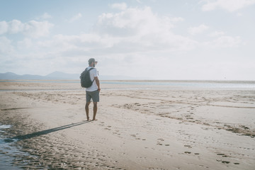Attractive muscular bearded man standing on the sea shore at sunrise with backpack and looking horizon