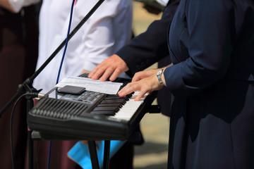 Kobieta w stroju zakonnicy gra na organach elektronicznych.