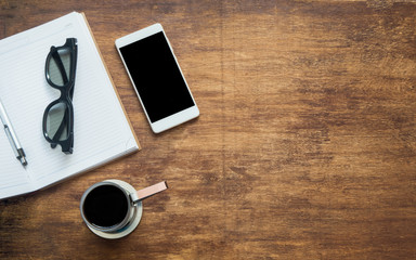 Coffee with blank notebook, glasses and phone with black blank space, flat lay