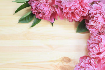 Pink peonies bouquet on light natural wood background as template for mothers day or birthday greeting card with copy space for text. Floral greeting card concept.