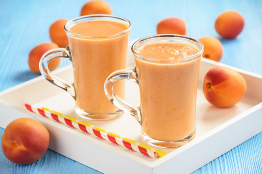 Apricot smoothie, healthy beverage, on wooden background.