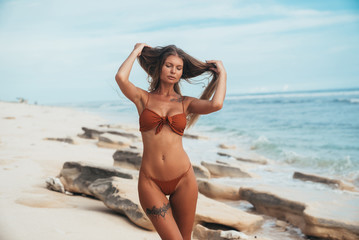 A sexy tanned tattooed model with a smooth skin and a gentle face posing on the seashore. The wind plays with the girl's hair, she adjusts them with her hands.