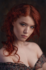 Dramatic retro portrait of a young beautiful dreamy redhead woman. Soft vintage toning.