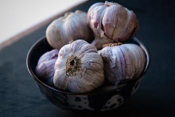 Garlic. Fresh garlic bulbs in vintage bowl over dark stone background. Top view on dark stone table.
