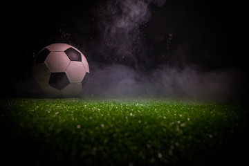 Traditional soccer ball on soccer field. Close up view of soccer ball (football) on green grass with dark toned foggy background.