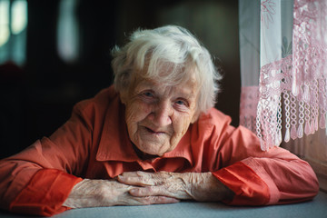Old woman sitting near window, close-up portrait.