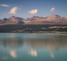 Landscape 3 peaks 3 clouds around lake Pukaki. Blue water