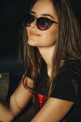 Close up portrait of a young beautiful caucasian girl with sunglasses smiling and looking into camera outdoor.