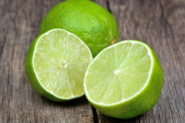 Fresh limes on wood background