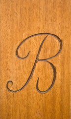 carved capital calligraphic letter b on a wood