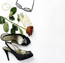 Woman fashion flatlay. Shoes, sunglasses, golden bracelets, parfume and red fresh rose  on white background.