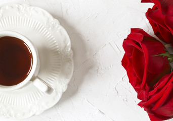 Cup of tea and red roses, top view