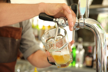 Bartender pouring fresh cold beer from tap, closeup