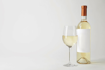 Bottle and glass with delicious wine on white background